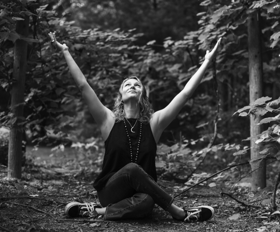 Woman in yoga position with hands reaching to the sky